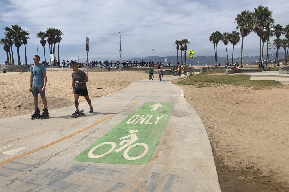 People walking on bike path on venice beach